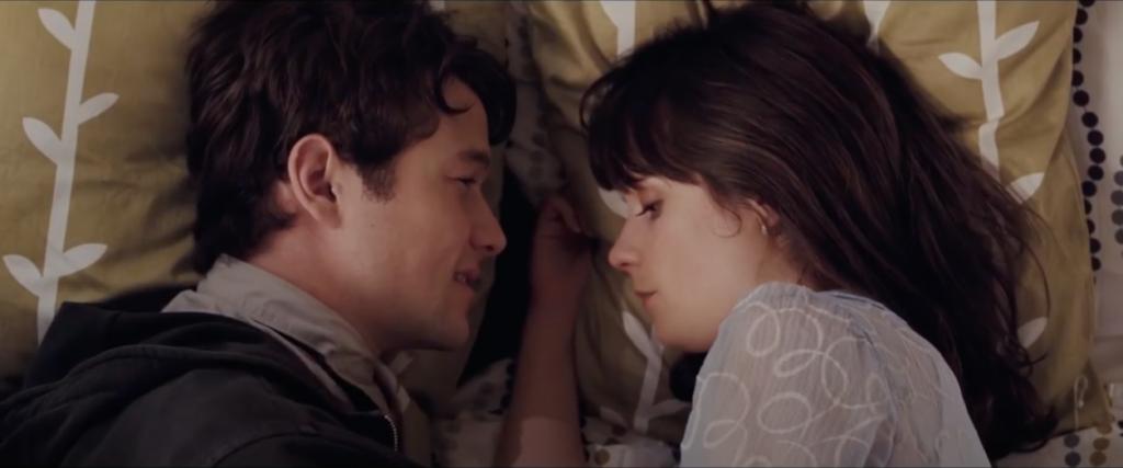 Plan rapproché épaule sur les deux personnages qui sont face à face dans un lit à IKEA.