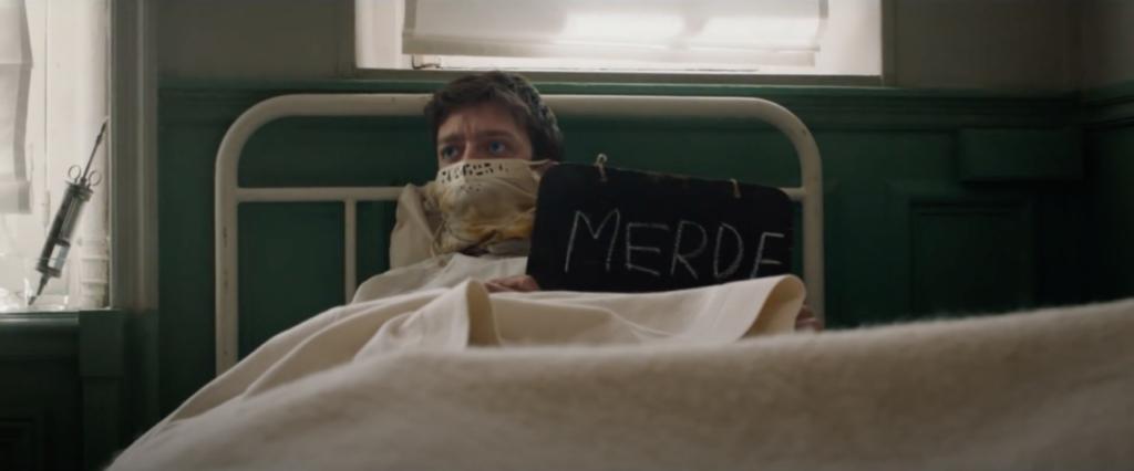 """Edouard dans son lit d'hôpital avec une pancartes où il a écrit """"merde""""."""
