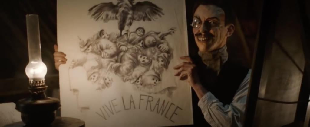Edouard qui montre l'un de ses dessins pour les monuments aux morts.