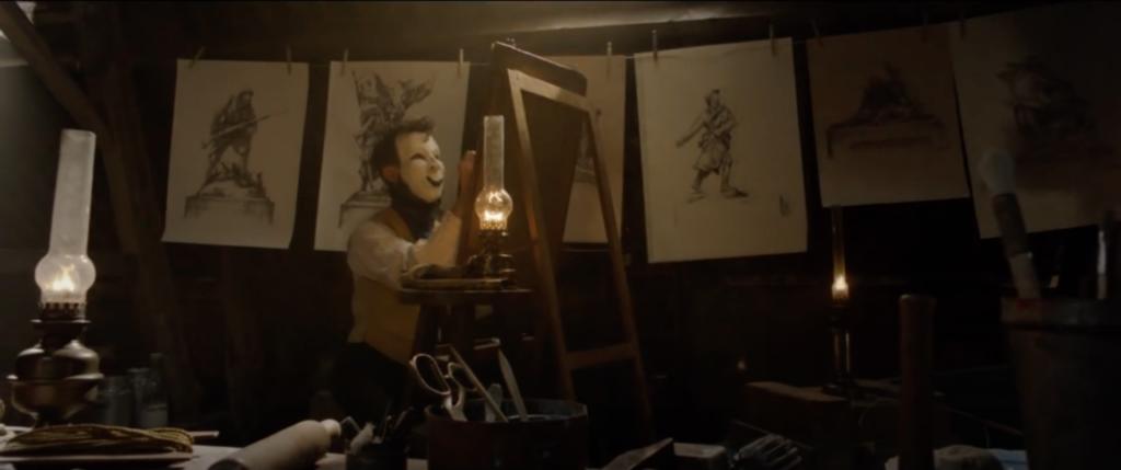 Edouard devant un chevalet avec plein de dessins autour de lui.