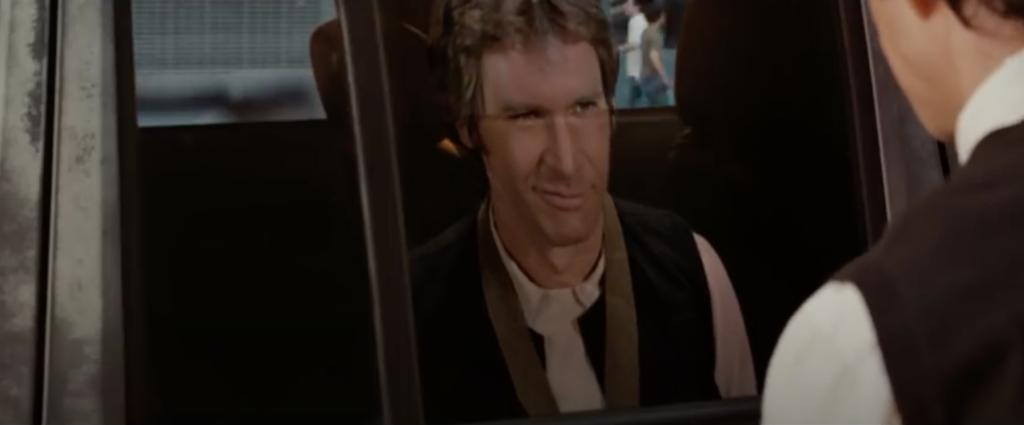 Han Solo fait un clin d'oeil à Tom dans le reflet de la vitre d'une voiture.